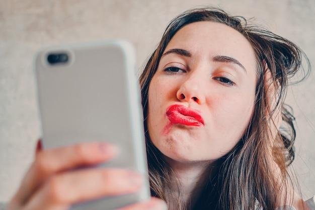 口紅にまみれて酔っ払った女の子が電話で自分撮り写真を撮る。