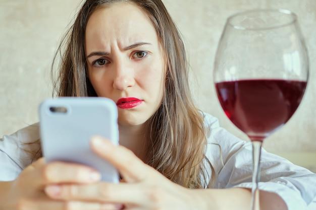 真面目な女の子がスマホを見てワインを飲む