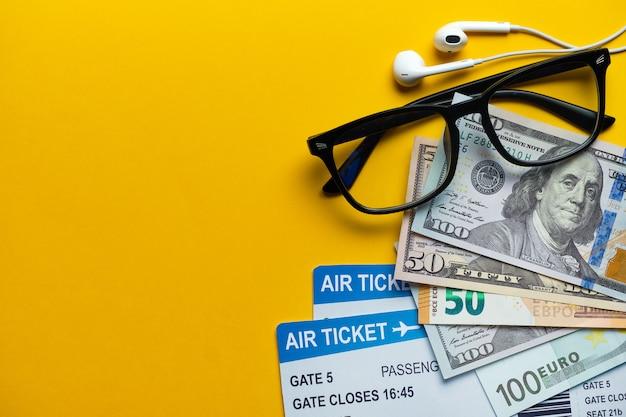 Концепция путешествия - очки, деньги, авиабилеты и наушники на желтом с копией пространства