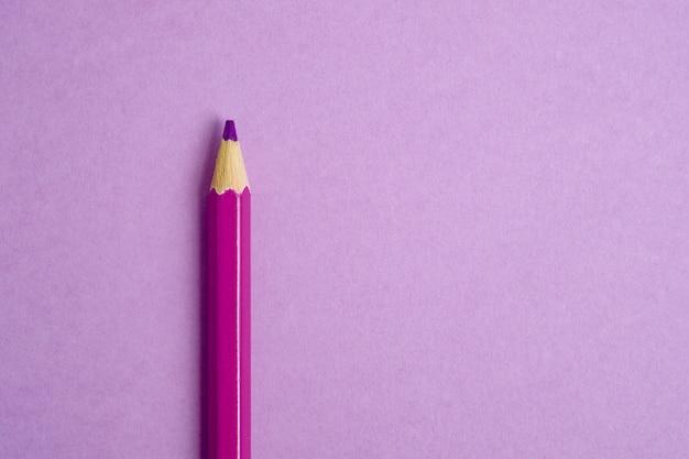 ピンクの紙の背景にピンクの鉛筆。閉じる。