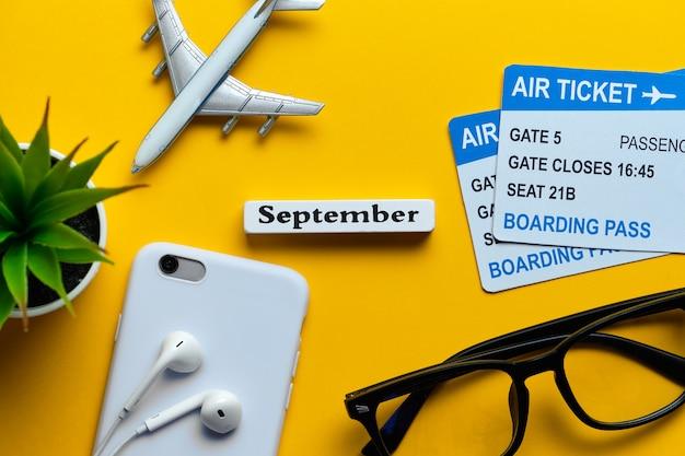 Концепция каникул в сентябре с авиабилетами на желтой предпосылке.