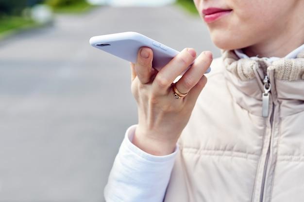 少女は通りの夏にスマートフォンで音声メッセージを話します。