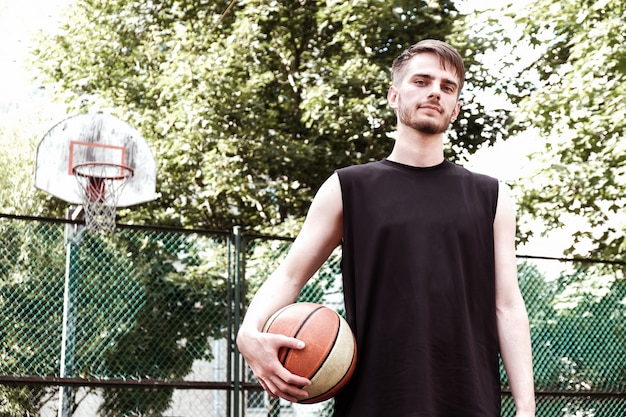 練習と通りでボールでポーズのバスケットボール選手