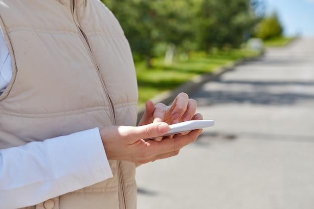 少女は通りを歩きながらスマートフォンを使用しています。