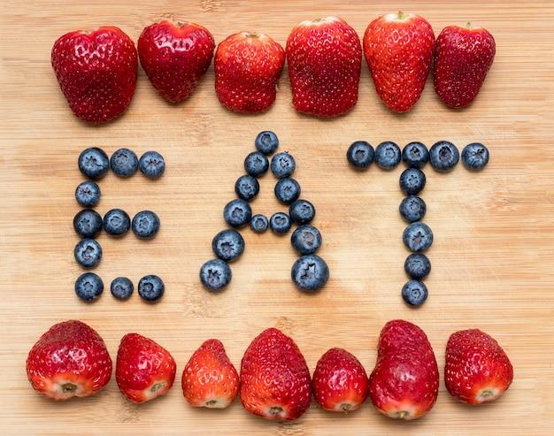 木製のイチゴとブルーベリーで形成された単語を食べる。
