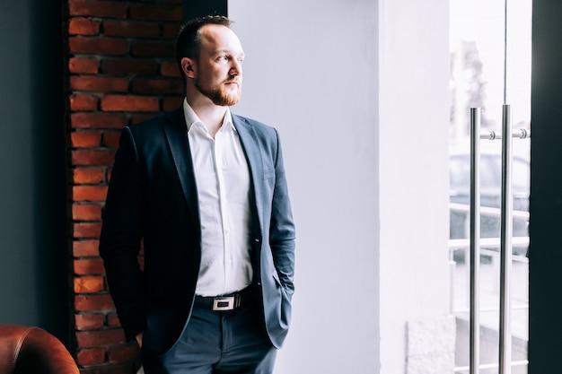 スーツで成功した実業家はオフィスに立って、ガラスのドアから外を眺めます。