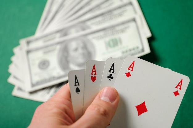 Рука держит четыре туза на зеленом фоне с долларом.