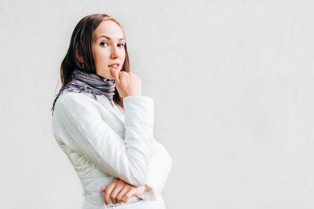 若い白人ブルネットは彼女の唇に親指をコケティッシュに置き、レンズに見えます。