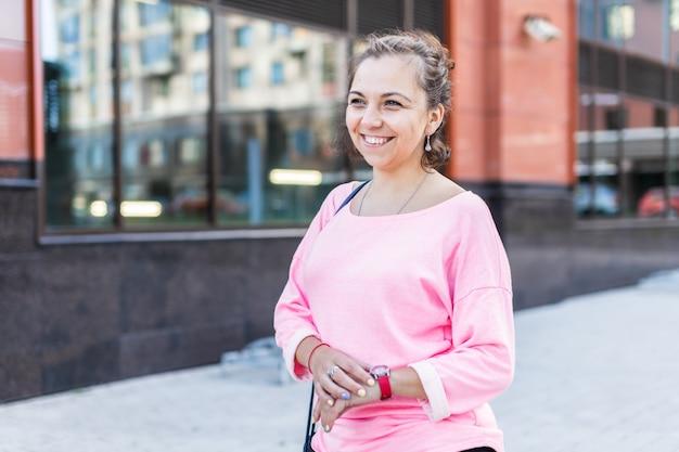幸せな若い白人女性の肖像画は彼女の腕時計に触れる
