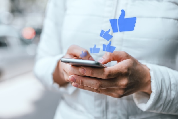 Молодая девушка с помощью смартфона получает лайки в социальных сетях.