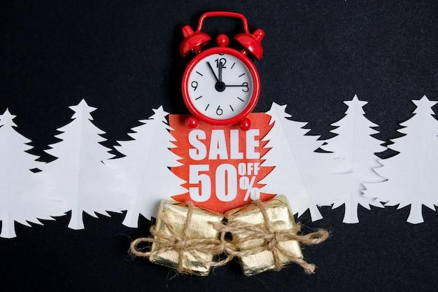 クラフト封筒と紙のクリスマスツリーと赤い割引ステッカーのギフトボックスとヴィンテージ時計