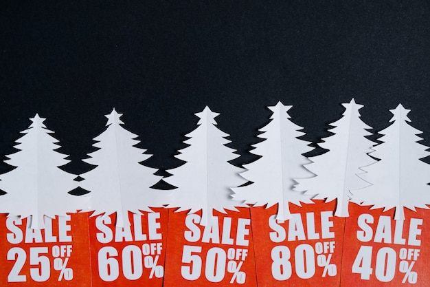 赤い割引カードと紙のクリスマスツリー