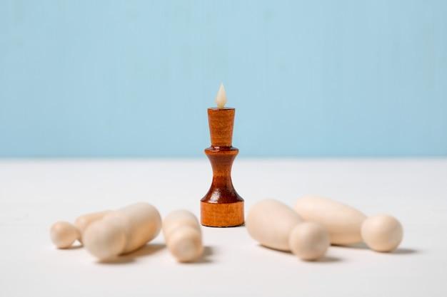 競争の概念、適者の勝利。横になっている人物の前にある木製の王の姿。