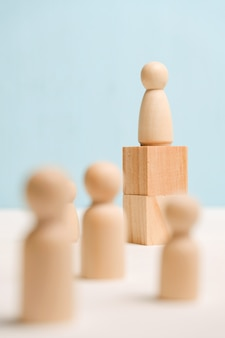Деревянные фигуры с кубиками на синем фоне. концепция бизнес-форума и обучения. закройте