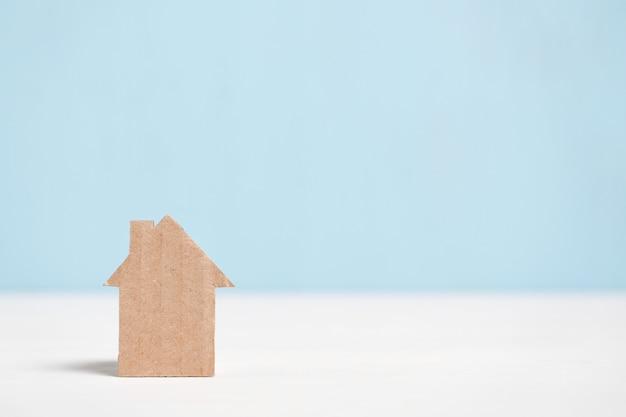青色の背景に抽象的な段ボールの家