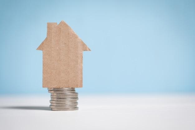 Абстрактный картонный дом на стопку монет.