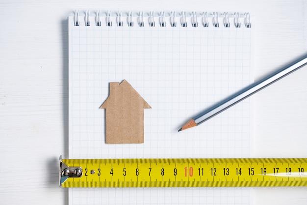 Картонный вырез дом, рулетка и карандаш на чистый лист спирали ноутбука.
