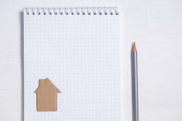 Дом картона на чистом листе спиральной тетради, карандаша на белизне.