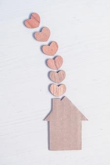 近くの木から心で抽象的な段ボールの家。快適さ、家族の暖かさ。