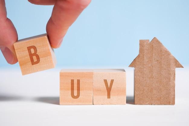 Абстрактный дом из картона рука держит куб, слово купить. покупка дома.