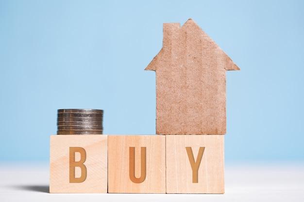 Абстрактный картонный дом рядом с монетами, слово купить на кубиках. накопление денег на жилье.