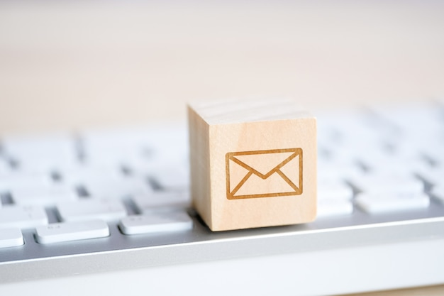 彼の手でメールシンボル封筒のイメージを持つ木製キューブ。連絡先。