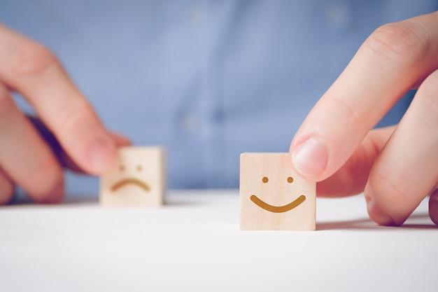 Мужчина держит пальцами деревянный куб с положительным лицом рядом с недовольным. для оценки действия или ресурса.