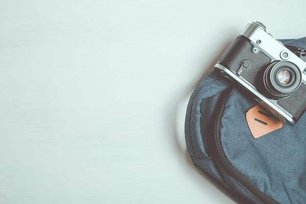 Ретро камера лежит на модном рюкзаке на белой деревянной предпосылке.