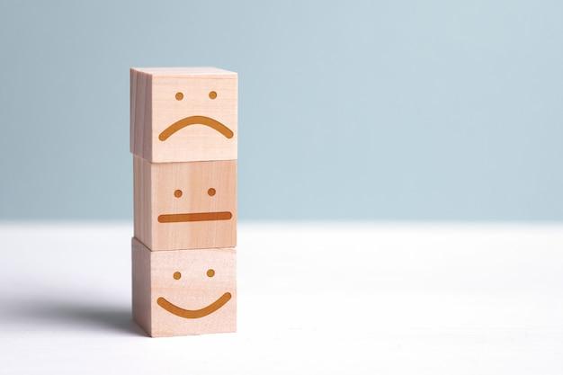 不愉快で中立的な人の横にあるポジティブな人のイメージを持つ木製キューブ。アクションまたはリソースを評価するため。