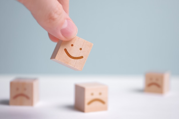Мужчина держит деревянный кубик с изображением позитивного лица на фоне негативных эмоций.