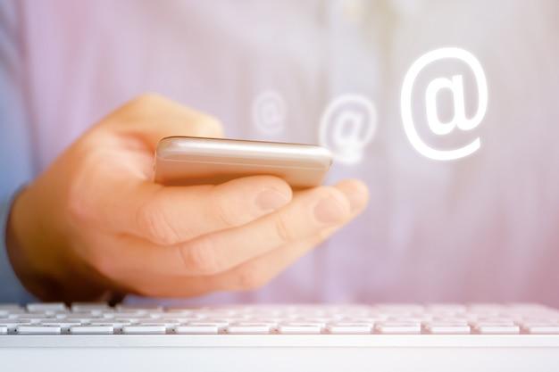 Мужчина в рубашке держит телефон рукой. абстрактный значок электронной почты. концепция обратной связи в интернете. закройте