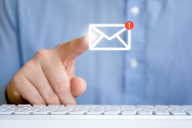 キーボードの前にシャツを着た男。新しいメッセージと抽象的なメールアイコン。インターネットフィードバックの概念。