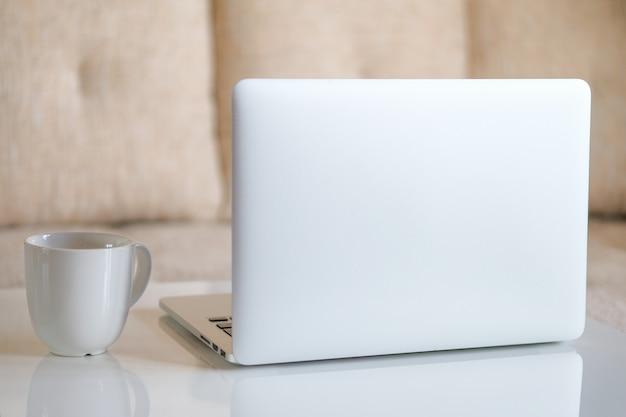 部屋のテーブルに白いマグカップと灰色のラップトップ。自宅で働きます。閉じる。
