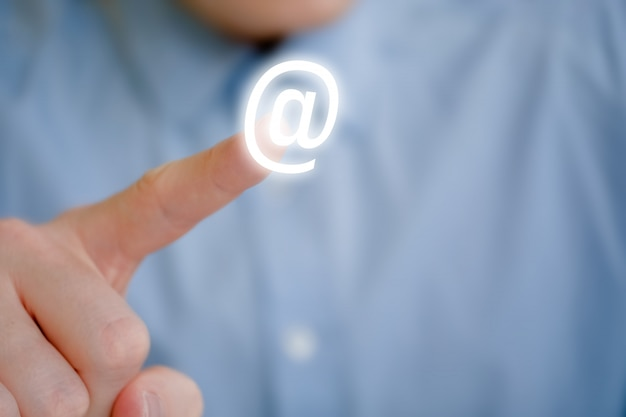 Мужской палец указывает на значок электронной почты. обращение с просьбой отправить письмо.