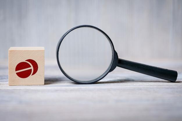 丸薬アイコンと拡大鏡のキューブ。検索医療情報、健康の概念。