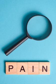 Концепция поиска, изучения, проведения исследований признаков боли. черное увеличительное стекло рядом со словом. вертикальная.