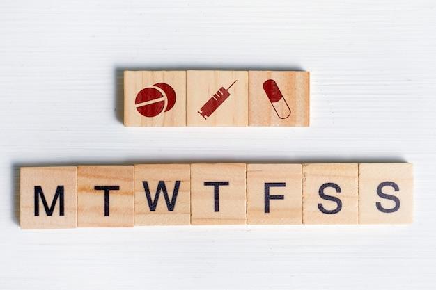 スケジュールに沿って薬と抗生物質を注射するというコンセプト-曜日。アイコン-タブレット、カプセル、注射器、手紙と木製の正方形。