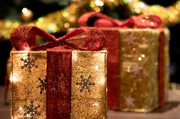 Декоративные коробки с подарками под елку украшены гирляндой. концепция нового года.