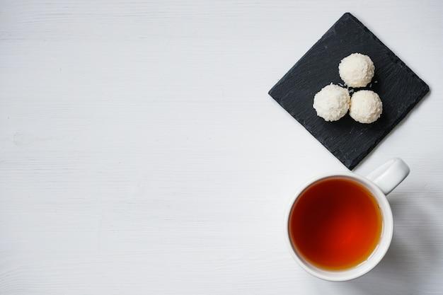 Белые шарики конфеты кокоса в тарелках сланца плиты на деревенской деревянной предпосылке с чашкой чаю.