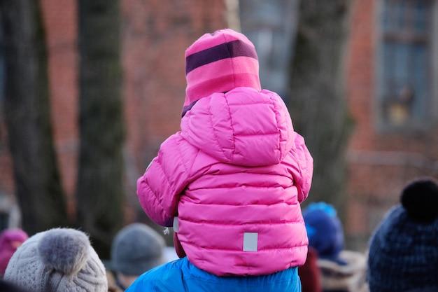 暖かい服を着た小さな子供が父親の首に座っています。通りを歩いています。