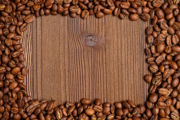 コーヒー豆は、木製の背景上のテキストで場所のフレームを作ります。