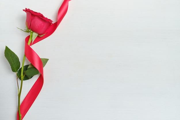 白い木製の背景にリボンで美しい赤いバラ。上面図。コピースペース。
