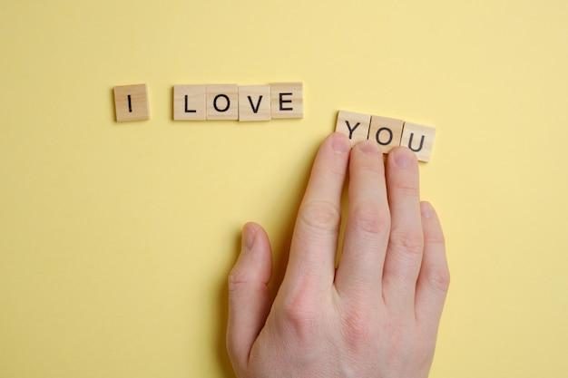 言葉-私はあなたを愛して-黄色の背景に木製の正方形から。手が数字を動かします。