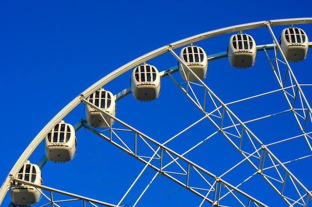 Большое красивое колесо обозрения в парке против голубого неба.
