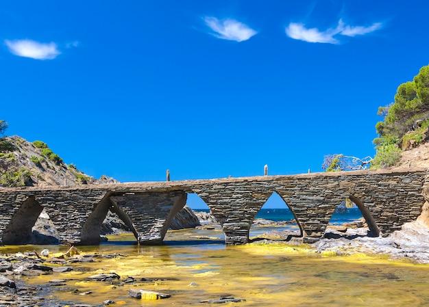 Каменный мост для туристов на побережье средиземного моря, кодакес, каталония