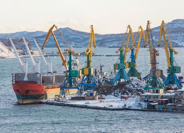 Зимний морской порт с кораблями и кранами