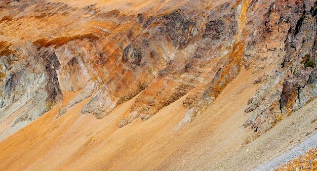 Скалистый склон вулкана вачкажец осенью. фон