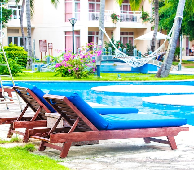 Лежаки и шезлонги с пляжными зонтиками возле бассейна в тропическом курортном отеле.