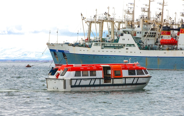 船はクルーズ船から岸へ人々を連れて行きます、