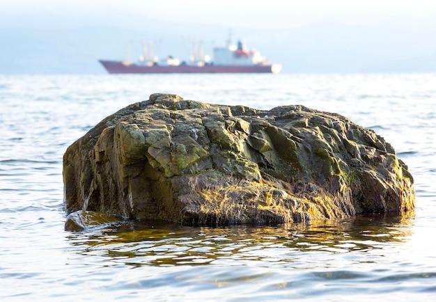 Камни на море и корабли на заднем плане,